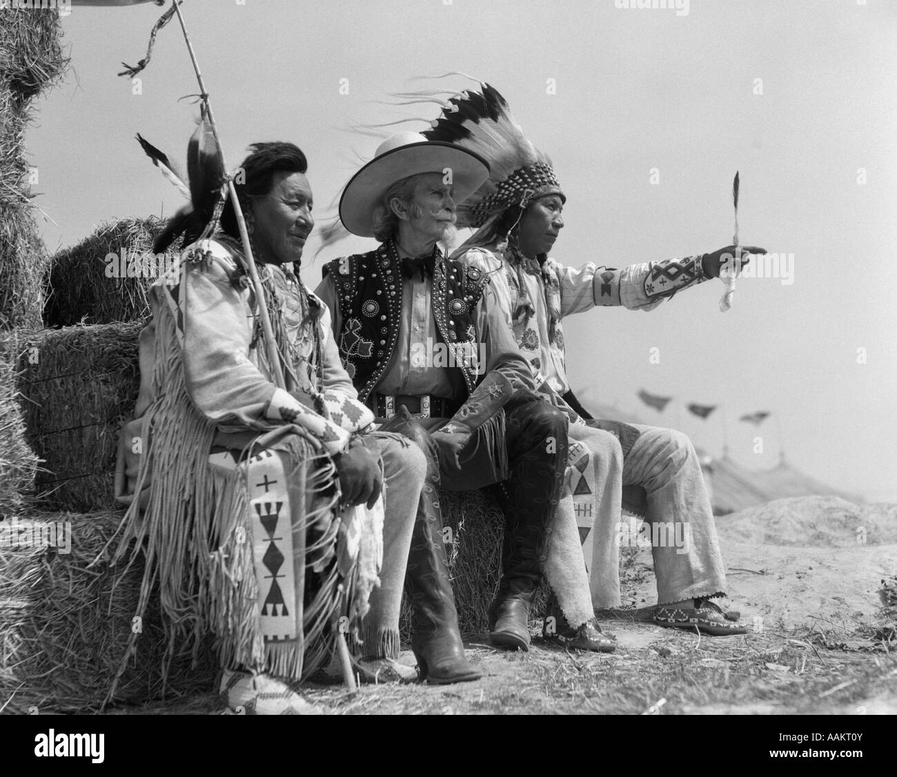 1940s PAIR OF INDIANS IN FULL COSTUME SITTING ON BALES OF HAY WITH COWBOY BETWEEN THEM - Stock Image