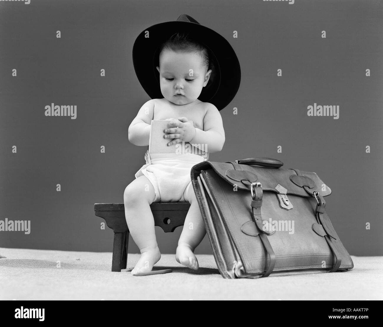 1940s BABY IN FEDORA SEATED ON STOOL WRITING IN NOTEBOOK WITH BRIEFCASE AT SIDE - Stock Image