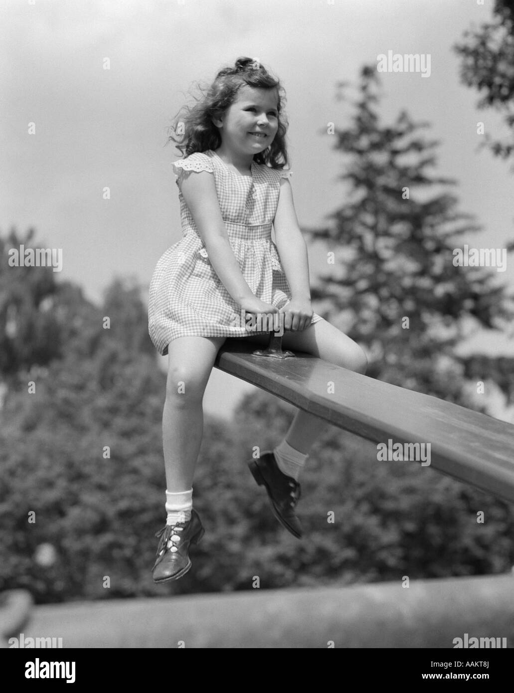 1950s 7 Year Old Girl Wearing Dress Sit On Seesaw Teeter