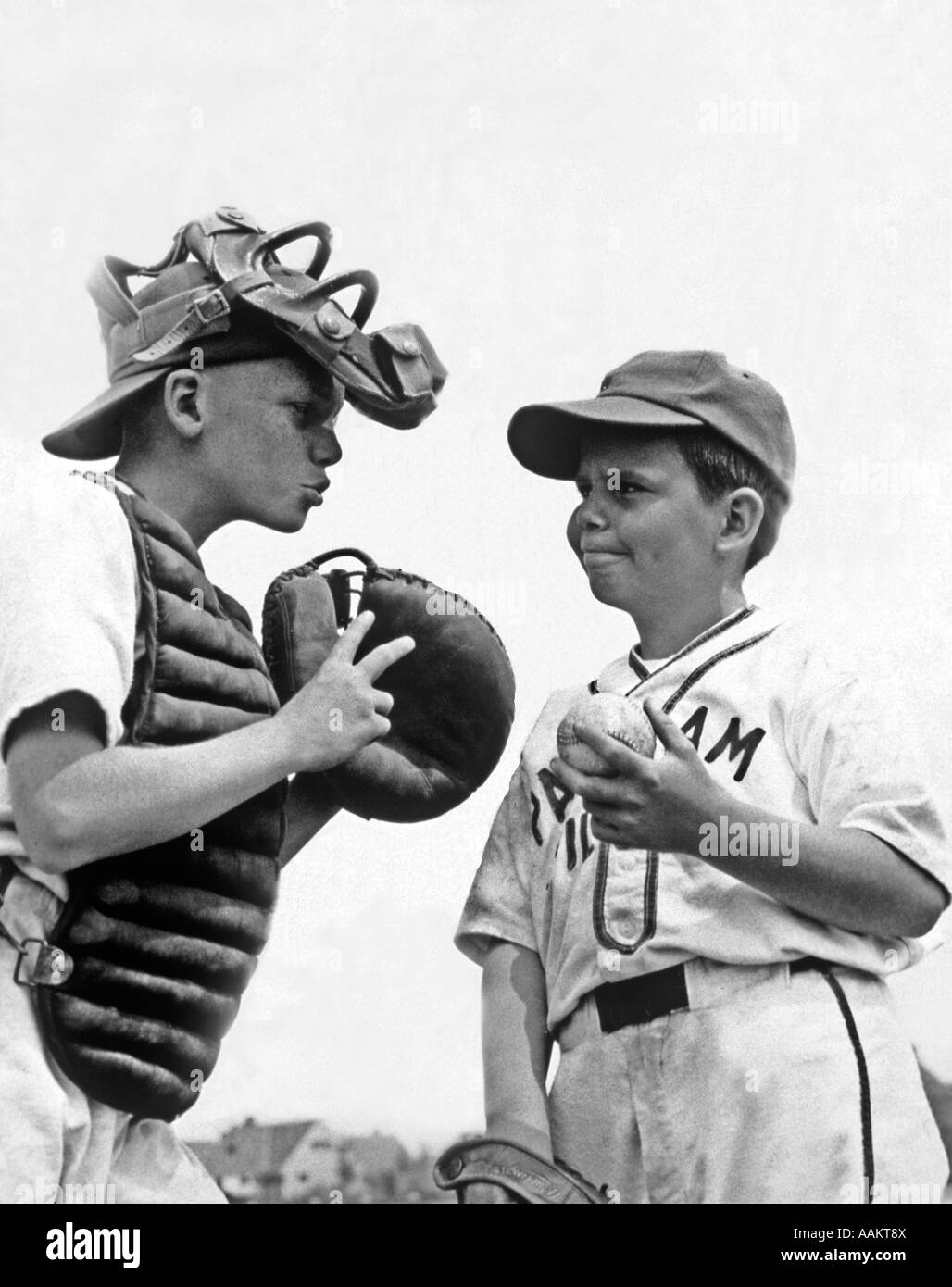 1950s TWO BOYS WEARING LITTLE LEAGUE BASEBALL UNIFORMS THE CATCHER IS GIVING ADVICE TO PITCHER - Stock Image