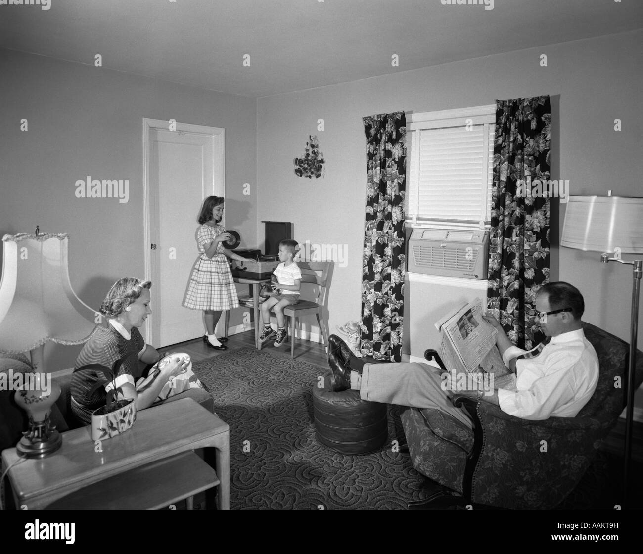 1950s FAMILY LIVING ROOM DAD NEWSPAPER MOTHER SEWING KIDS BOY GIRL RECORD PLAYER - Stock Image
