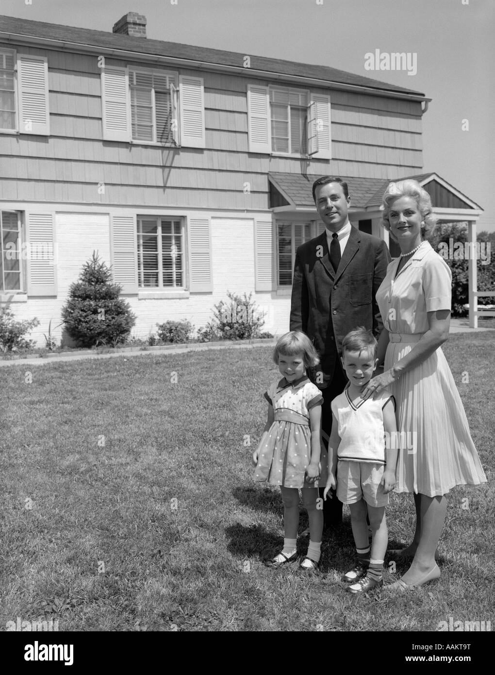 1960s FAMILY PORTRAIT STANDING BY SUBURBAN HOUSE - Stock Image