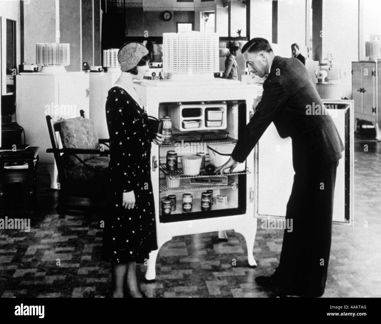 1920s 1930s SALESMAN DEMONSTRATING ELECTRIC REFRIGERATOR TO WOMAN SHOPPER - Stock Image