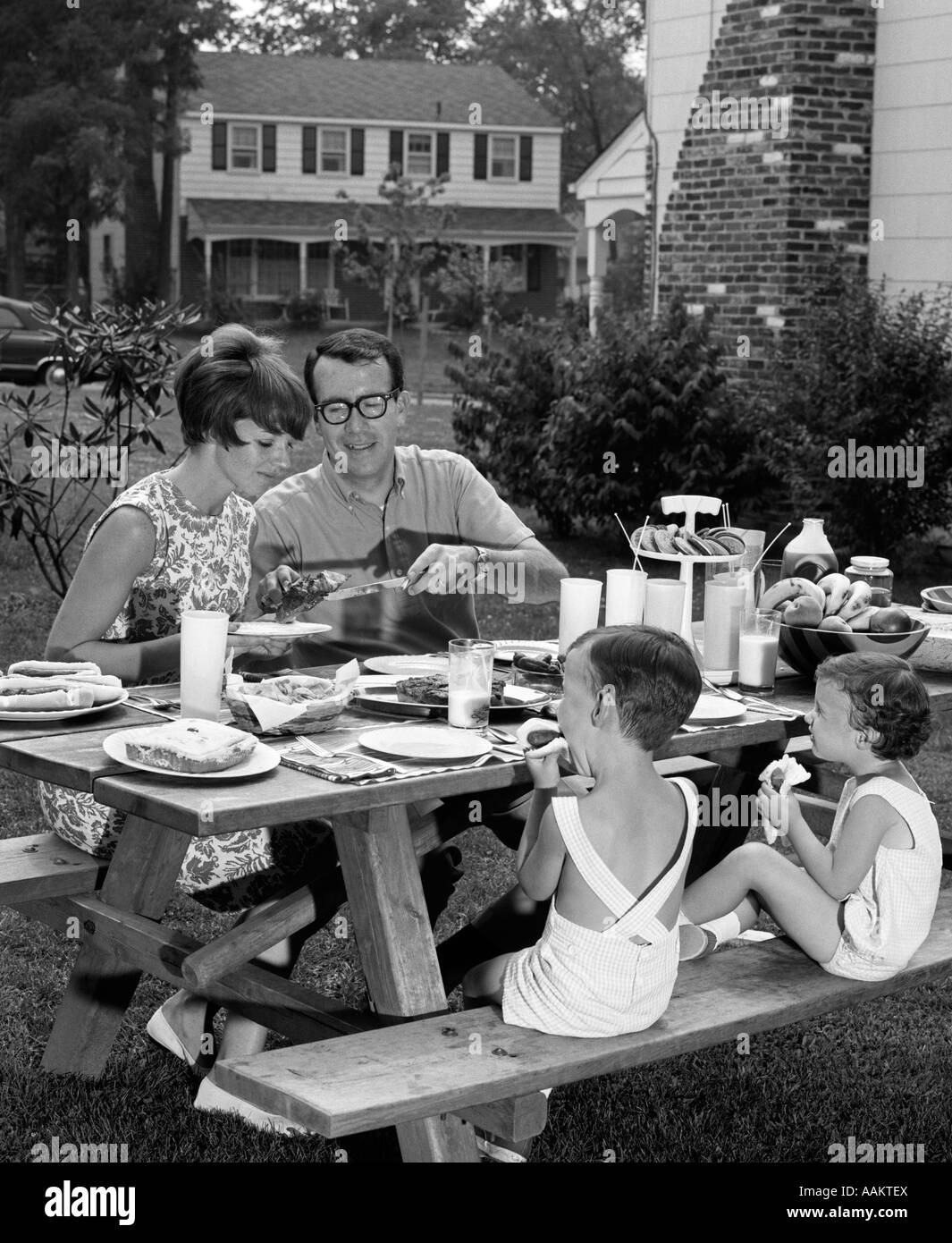 1960s SUBURBAN FAMILY OF FOUR AT PICNIC TABLE IN BACKYARD EATING - Stock Image