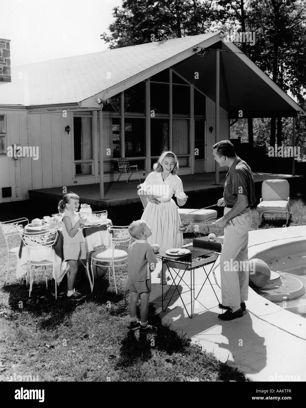 1950s FAMILY GRILLING HAMBURGERS BESIDE POOL IN BACKYARD COOKOUT - Stock Image