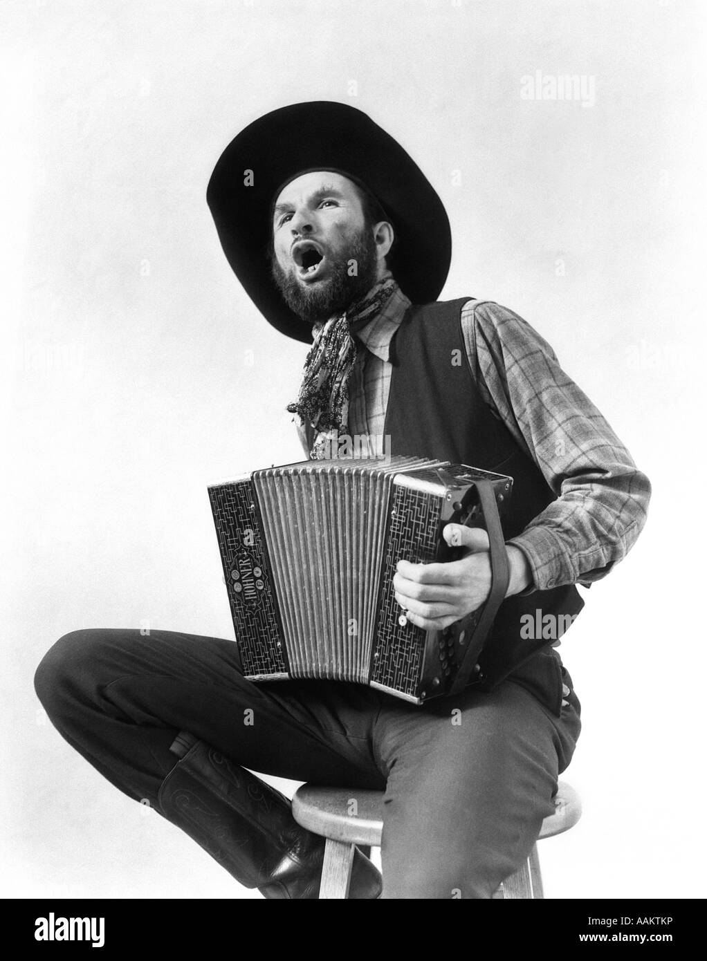 1930s COWBOY PLAYING ACCORDION & SINGING - Stock Image