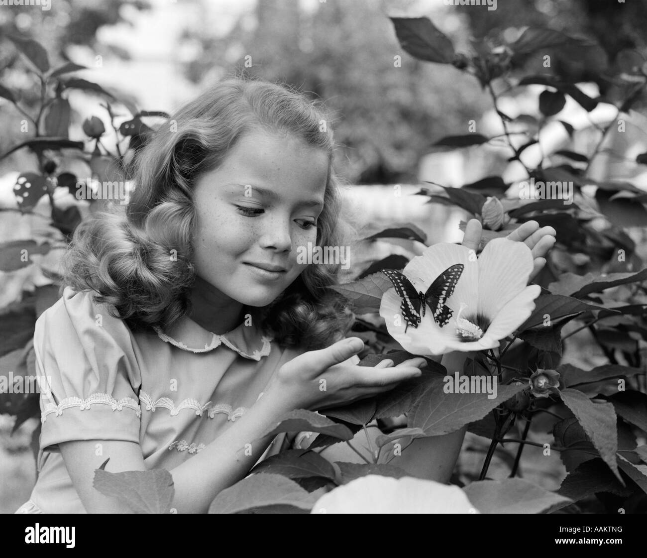 1950s Pretty Little Girl Smiling At Hibiscus Flower Butterfly In