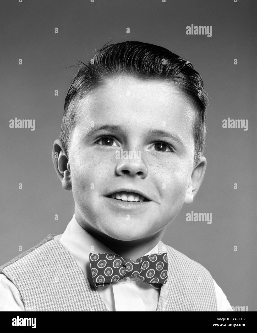 1950s SMILING PORTRAIT YOUNG MAN BOY WEARING CHECKERED VEST AND POLKA DOT BOW TIE - Stock Image