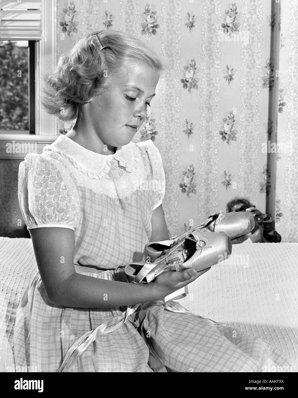 1950s YOUNG PRE-TEEN TEEN GIRL LOOKING WISTFULLY AT HER BALLET SLIPPERS - Stock Image