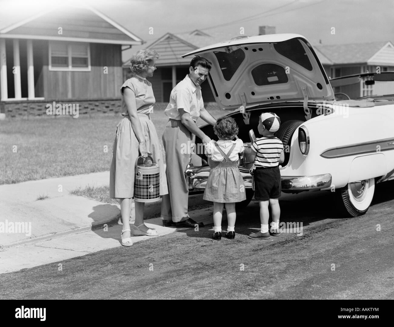 1950s FAMILY PACKING TRUNK OF CAR FOR A PICNIC - Stock Image