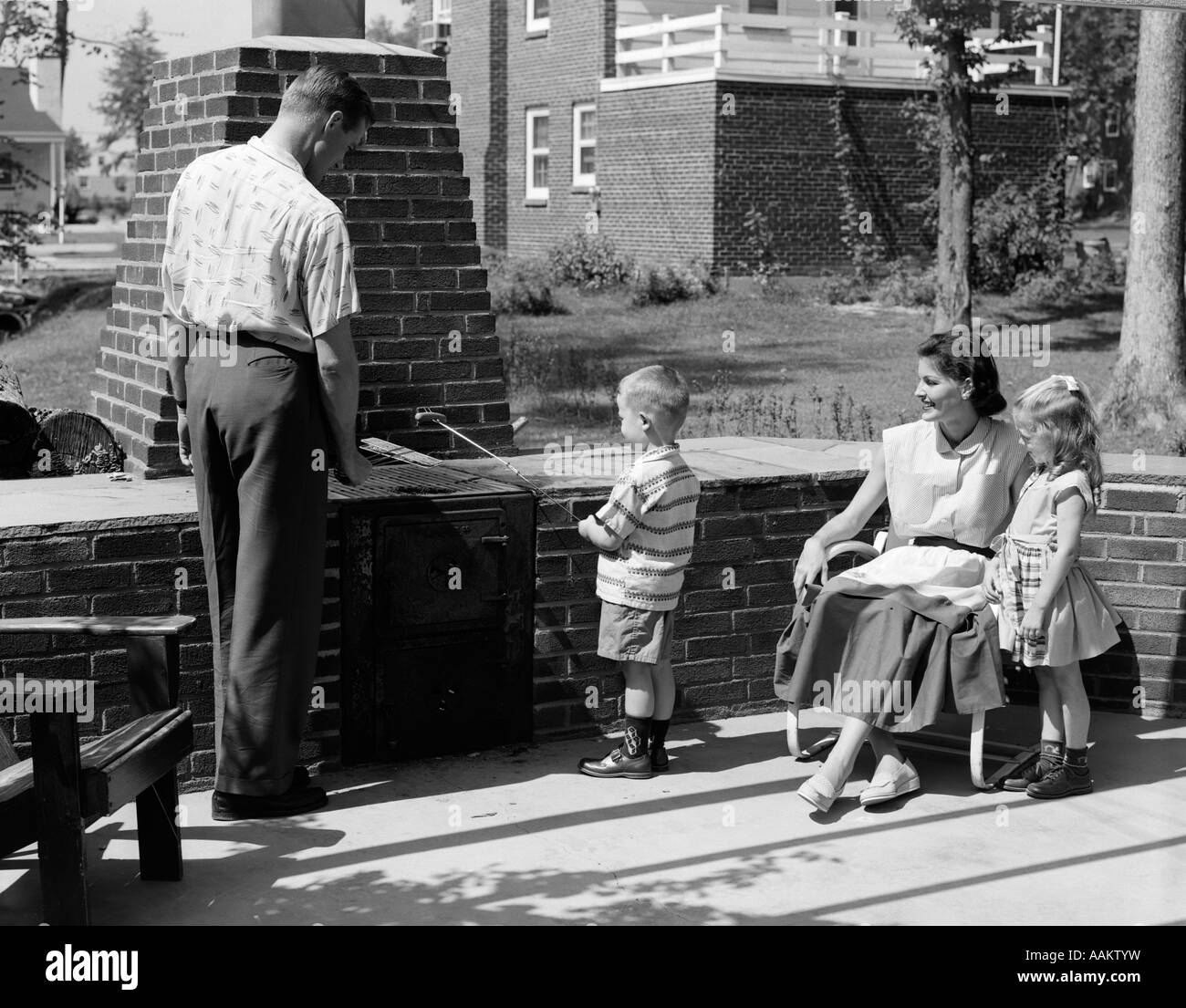 1950s FAMILY ON BRICKED BACKYARD PATIO LITTLE BOY COOKING HOT DOG ON SKEWER - Stock Image