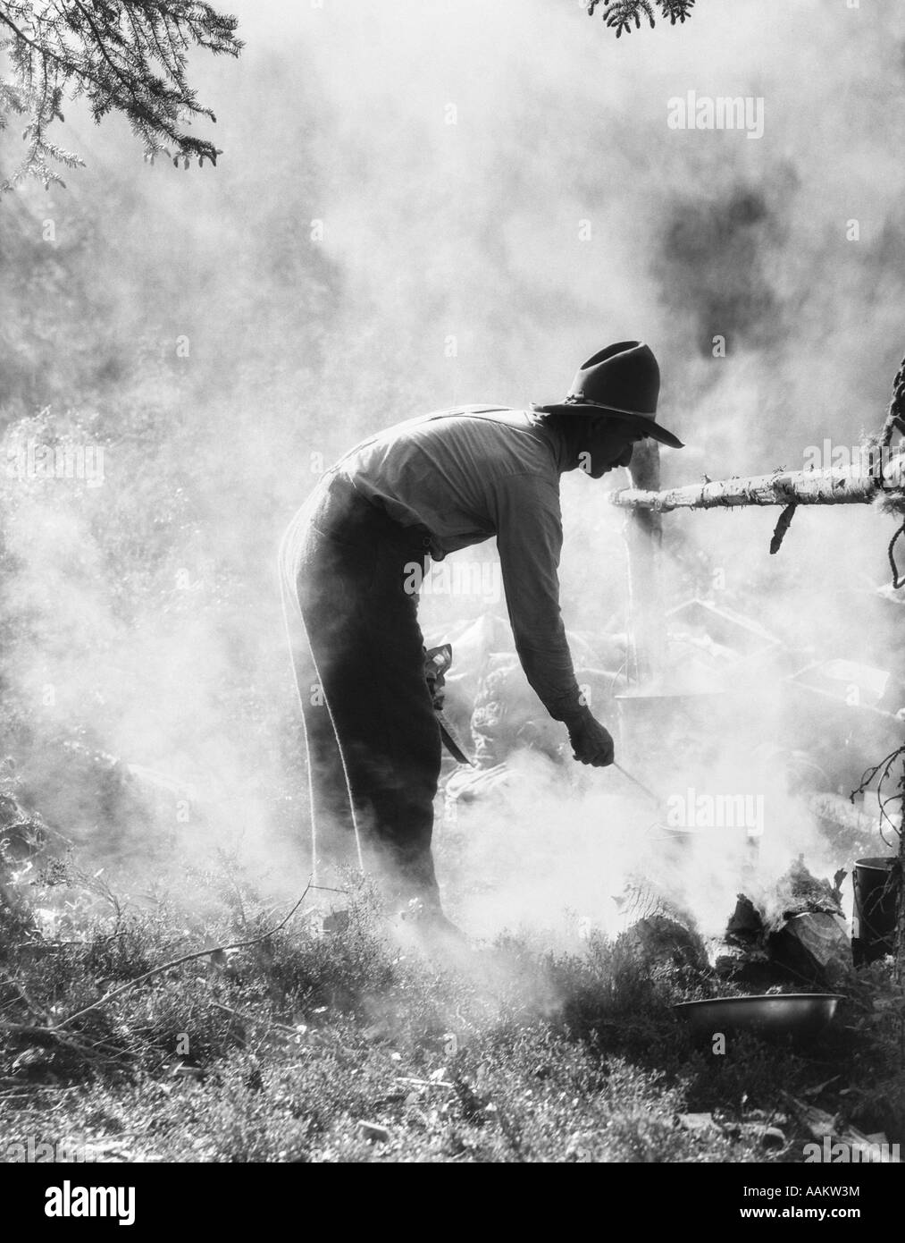 1920s 1930s MAN COWBOY COOK BENDING OVER CAMPFIRE - Stock Image