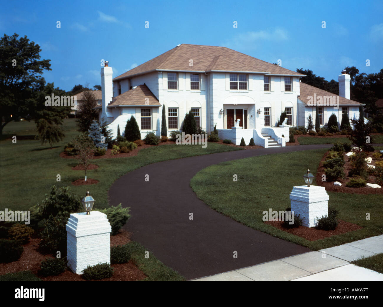 WHITE TWO STORY RESIDENTIAL HOME AND CURVED DRIVEWAY - Stock Image