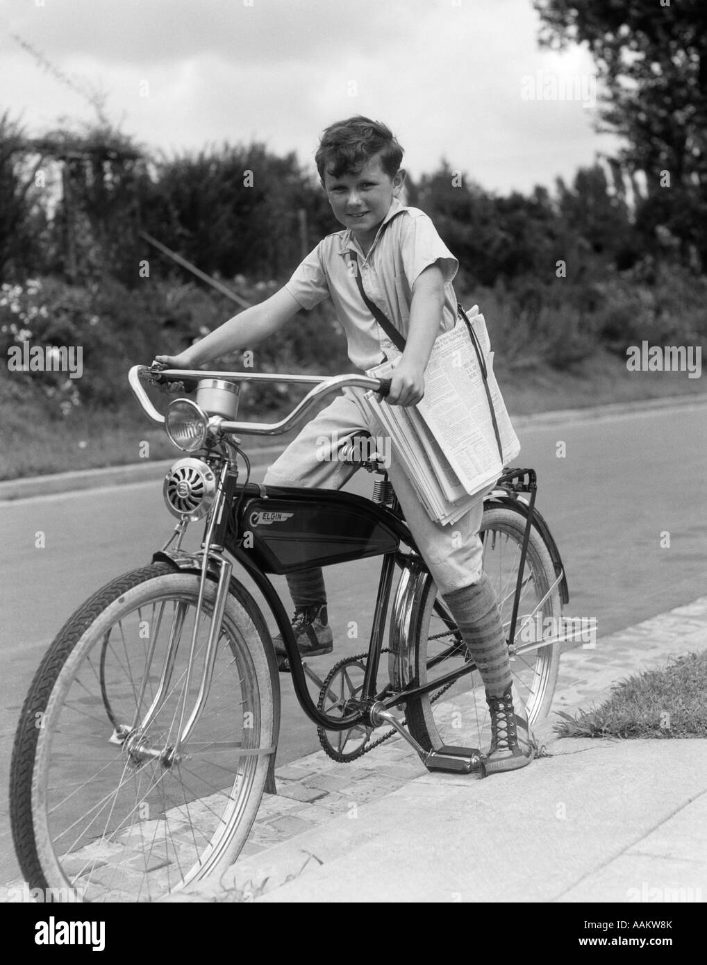 1940s BOY ON AN ELGIN BIKE CARRYING NEWSPAPERS IN A SLING WEARING KNEE SOCKS AND SNEAKERS - Stock Image