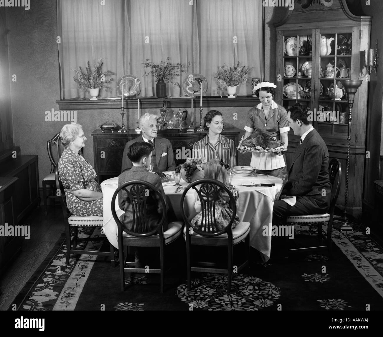 1940s TWO GENERATION FAMILY IN DINING ROOM THANKSGIVING TURKEY BEING SERVED  BY MAID