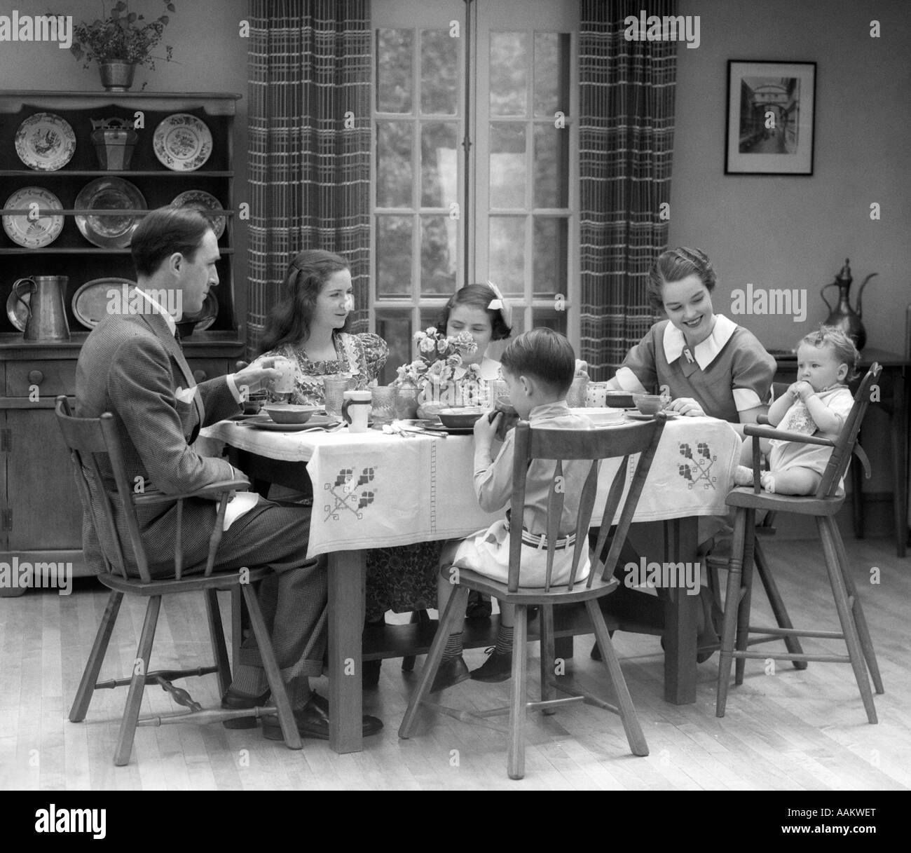 1930s FAMILY OF 6 SITTING AT THE TABLE IN A DINING ROOM EATING BREAKFAST THE BABY IS SITTING IN A HIGH CHAIR - Stock Image