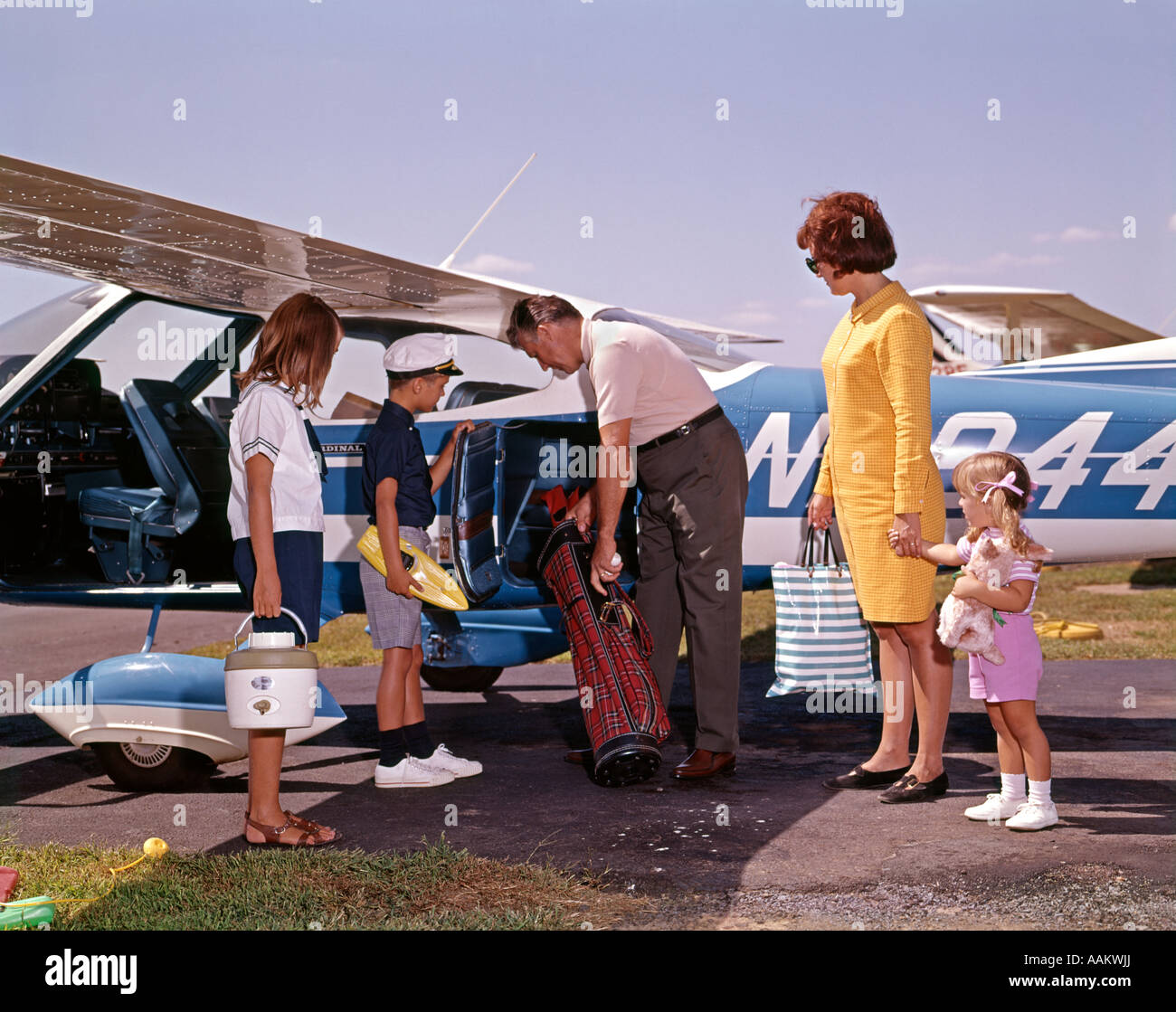 1960s FAMILY LOADING LUGGAGE ONTO PRIVATE PROP AIRPLANE PLANE TRAVEL VACATION MOTHER FATHER CHILDREN - Stock Image