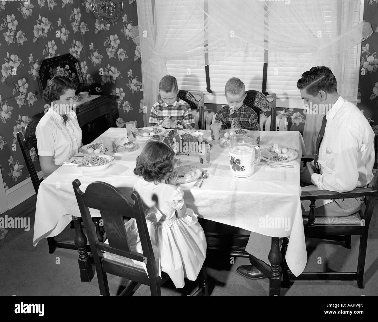 1950s FAMILY OF 5 MOM DAD 3 KIDS SITTING AT DINING ROOM TABLE SAYING GRACE  WITH HEADS BOWED