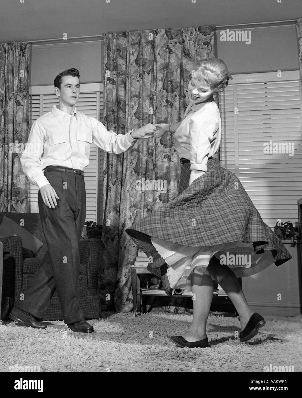 1950s TEENAGE COUPLE JITTERBUG DANCING TOGETHER IN LIVING ROOM - Stock Image