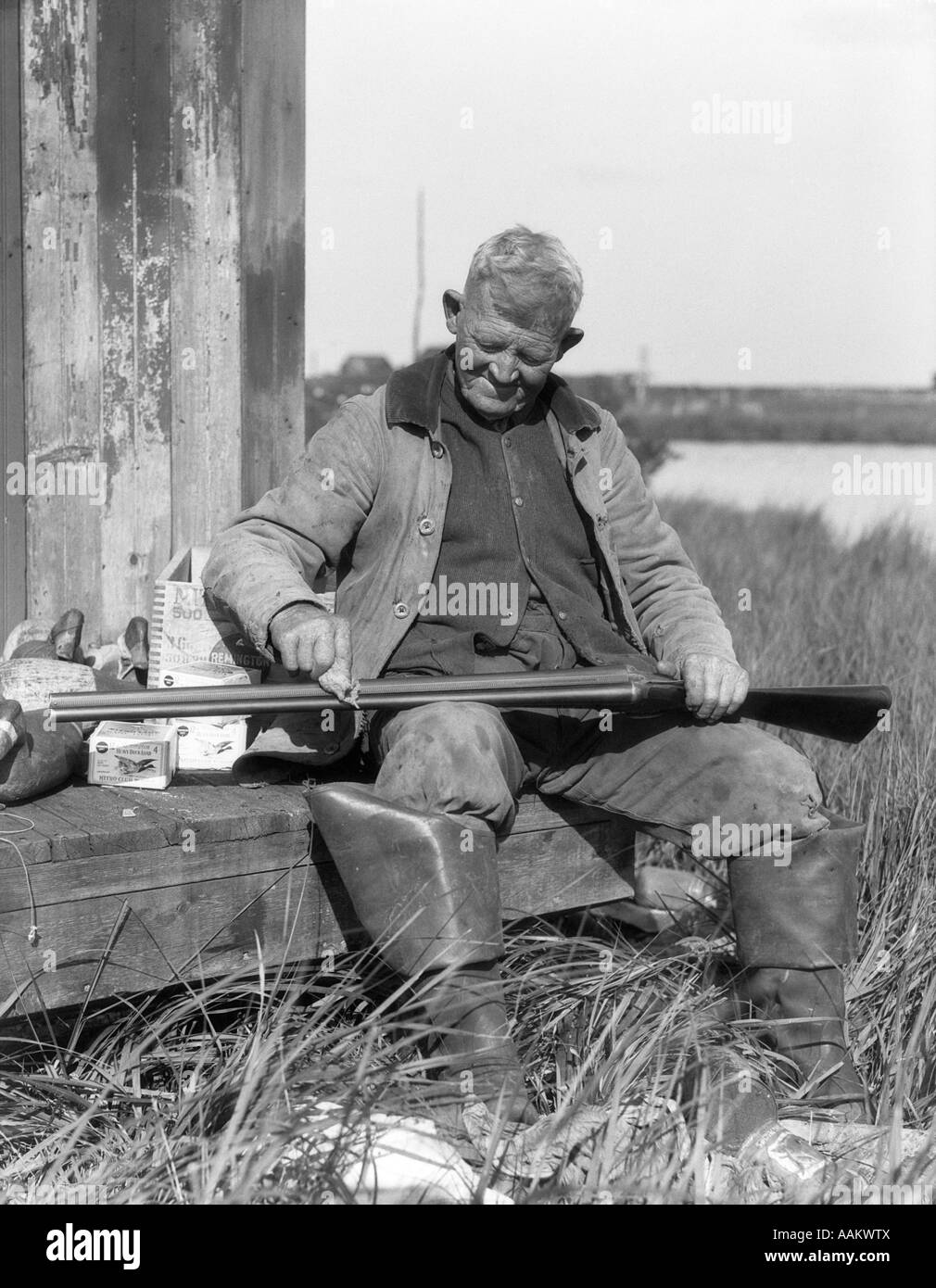1920s 1930s senior man sitting on bench cleaning duck