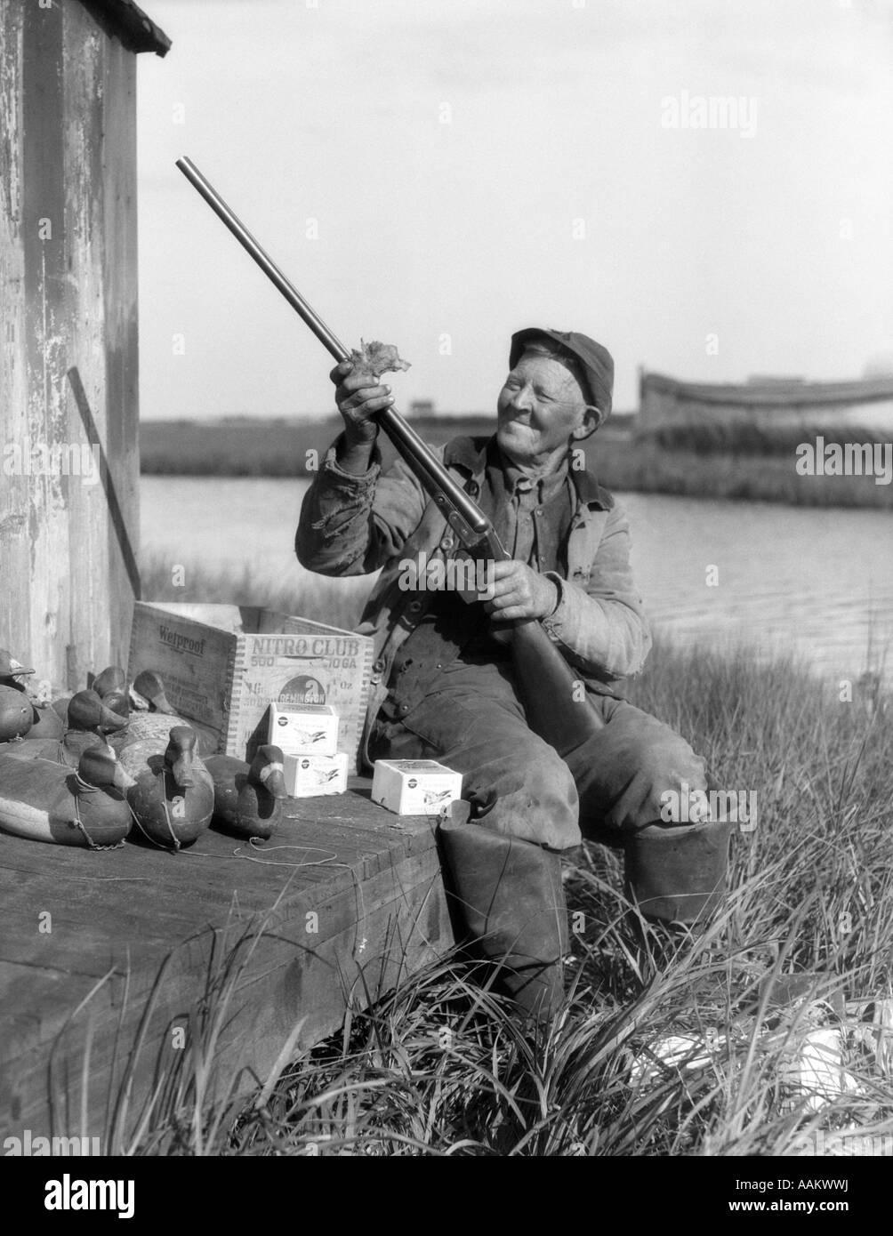 1920s SMILING SENIOR MAN CLEANING PARKER SHOTGUN SURROUNDED BY DUCK DECOYS AMMUNITION BOX BARNEGAT BAY, NEW JERSEY, - Stock Image
