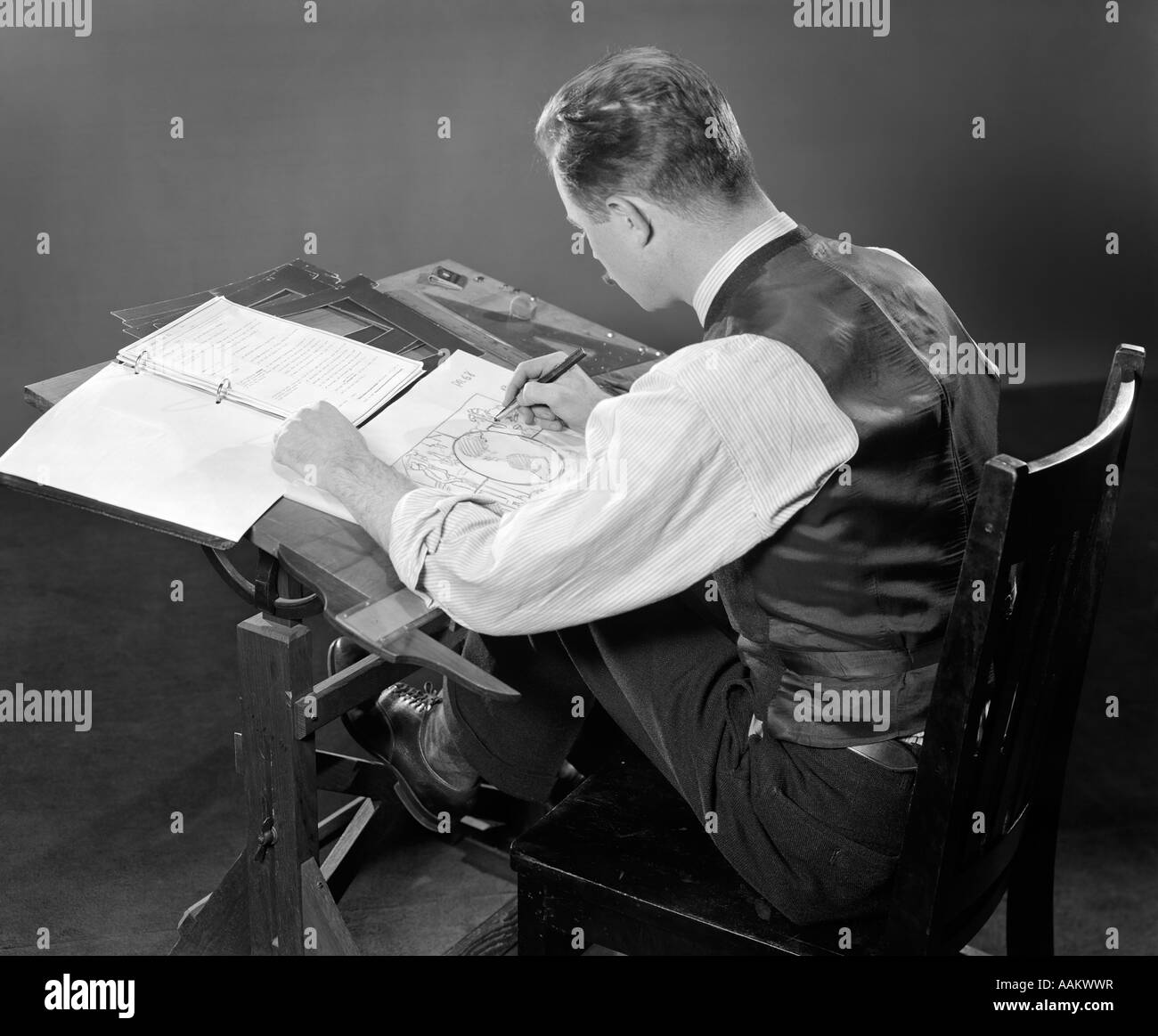1930s 1940s REAR HIGH ANGLE BACK VIEW MAN SEATED AT DRAFTING TABLE WORKING  DRAWING   Stock