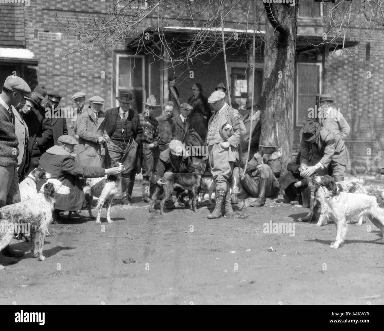 1920s 1930s HUNTING DOGS WITH TRAINERS ASSEMBLED FOR FIELD TRIALS IN FRONT OF BRICK BUILDING - Stock Image