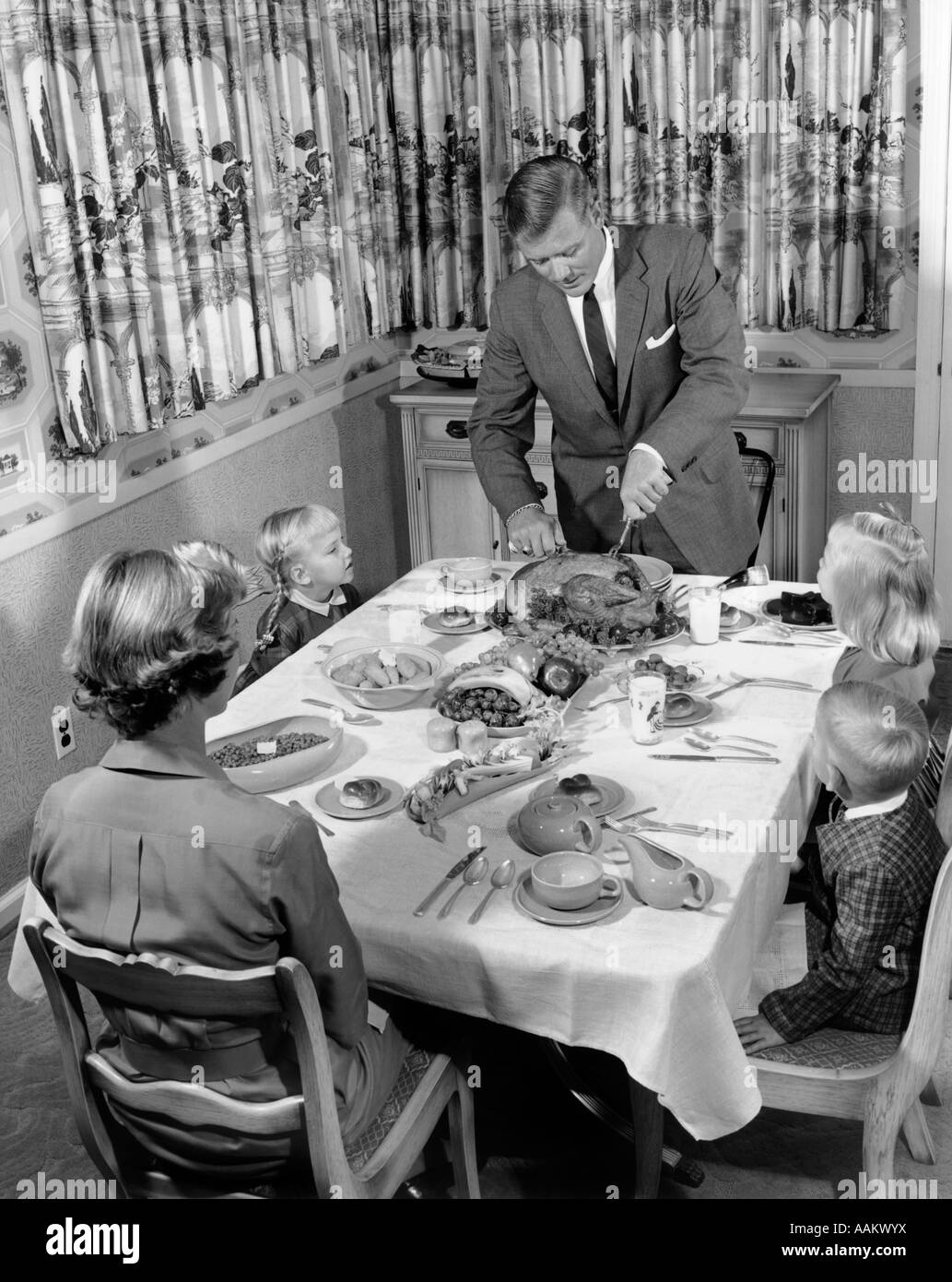 1950s FAMILY OF 5 AT DINING ROOM TABLE FOR THANKSGIVING DINNER WITH FATHER  CARVING TURKEY