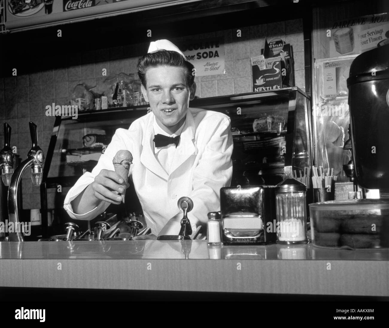 1950s SMILING YOUNG MAN SODA JERK LEANING ACROSS COUNTER LOOKING AT CAMERA SERVING ICE CREAM CONE Stock Photo
