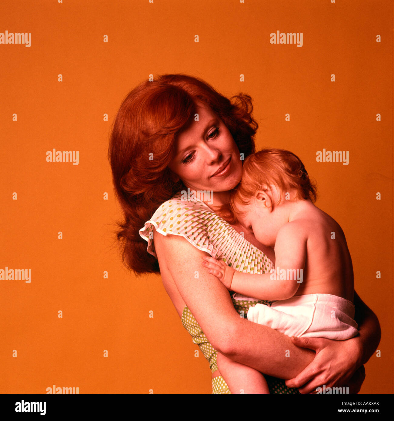 1970s PENSIVE SMILING RED HEADED MOTHER HUGGING RED HEADED BABY CHILD WEARING A DIAPER - Stock Image
