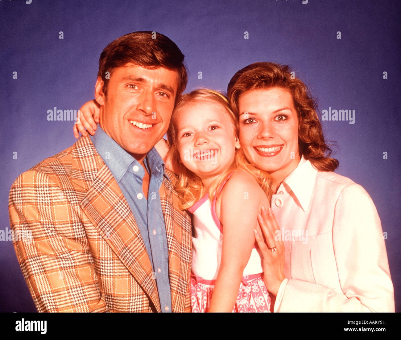 1970s HEAD SHOULDERS PORTRAIT SMILING FAMILY OF 3 - Stock Image