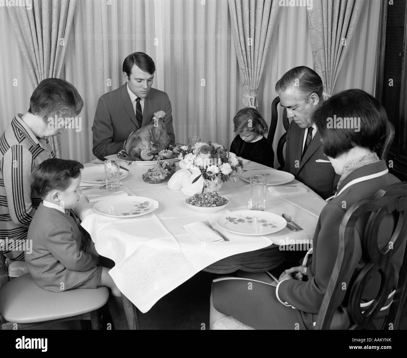 1960s THREE GENERATION FAMILY SAYING GRACE PRAYER AT THANKSGIVING TURKEY DINNER - Stock Image