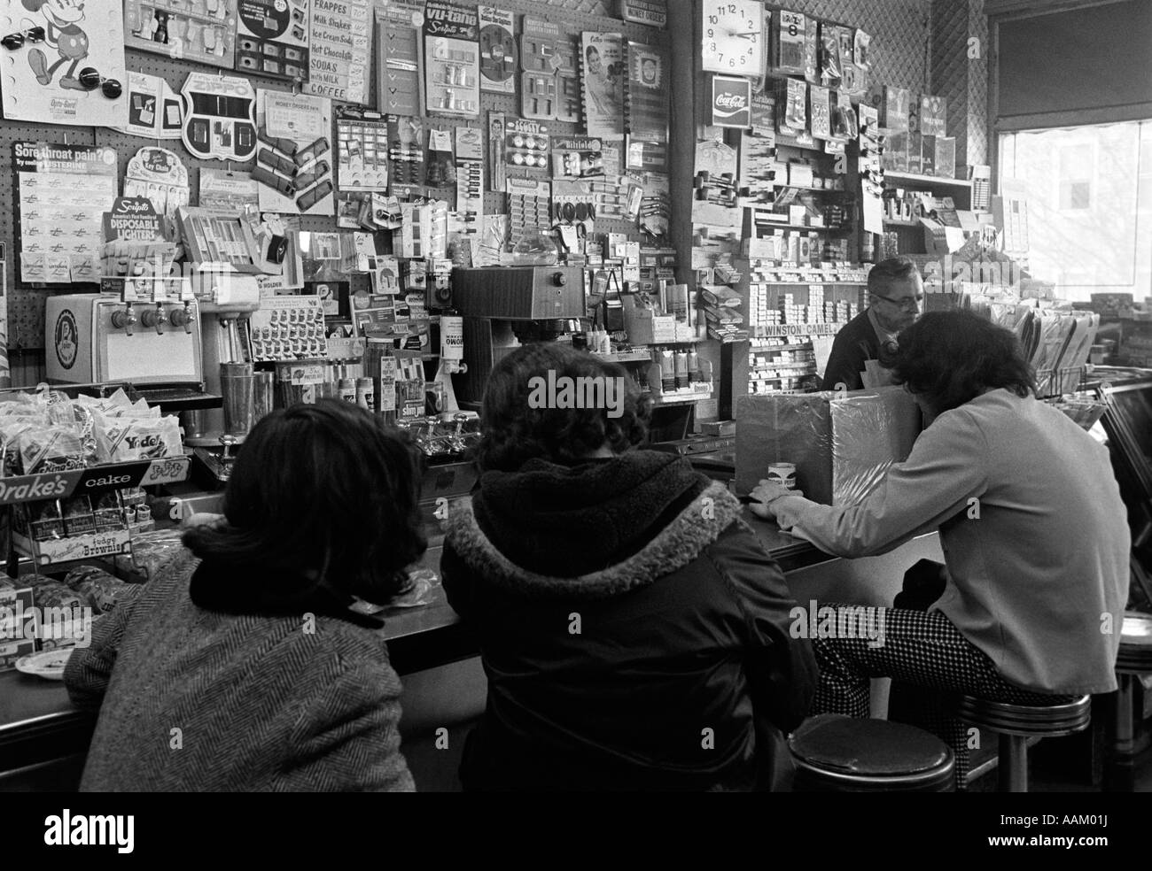 1970s 3 TEEN BOYS WITH BACKS TO CAMERA SITTING ON STOOLS AT THE COUNTER OF A SODA FOUNTAIN SHOP Stock Photo