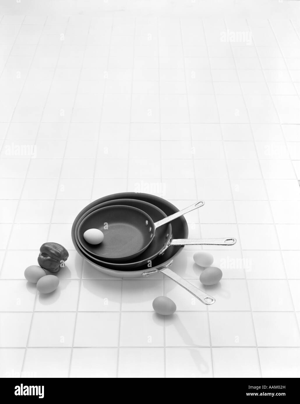 EGGS FRYING PANS TILE COUNTER - Stock Image
