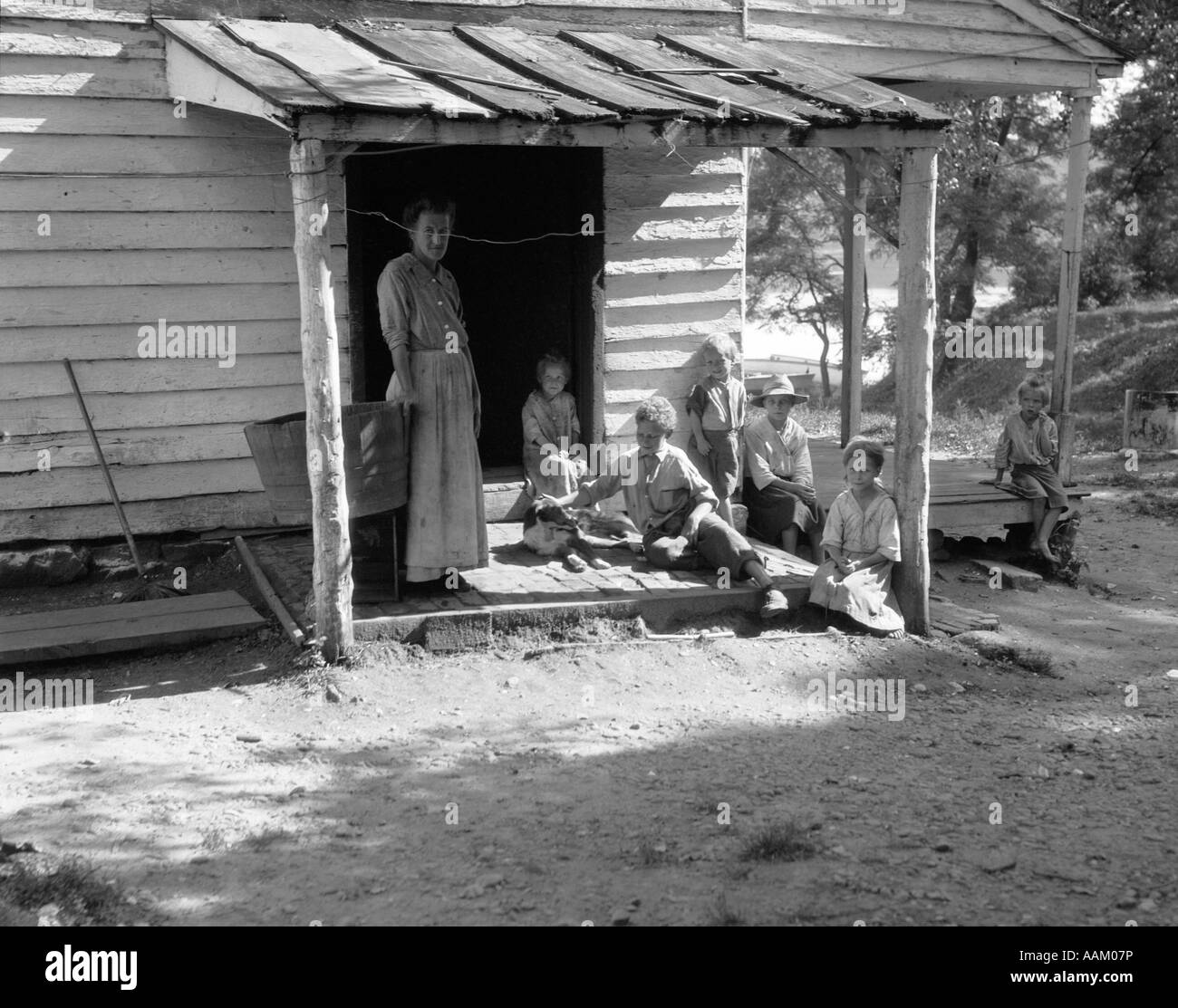 1930s 1940s Farm Woman With Six Children On Porch Of Clap