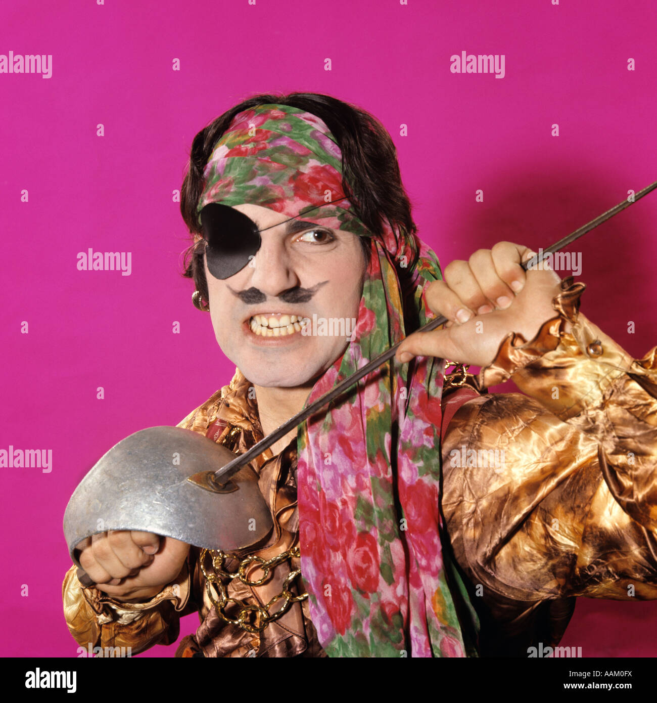 1970s CHARACTER MAN IN PIRATE COSTUME HOLDING A SWORD FUNNY FACE EXPRESSION MOUSTACHE GRITTING TEETH - Stock Image