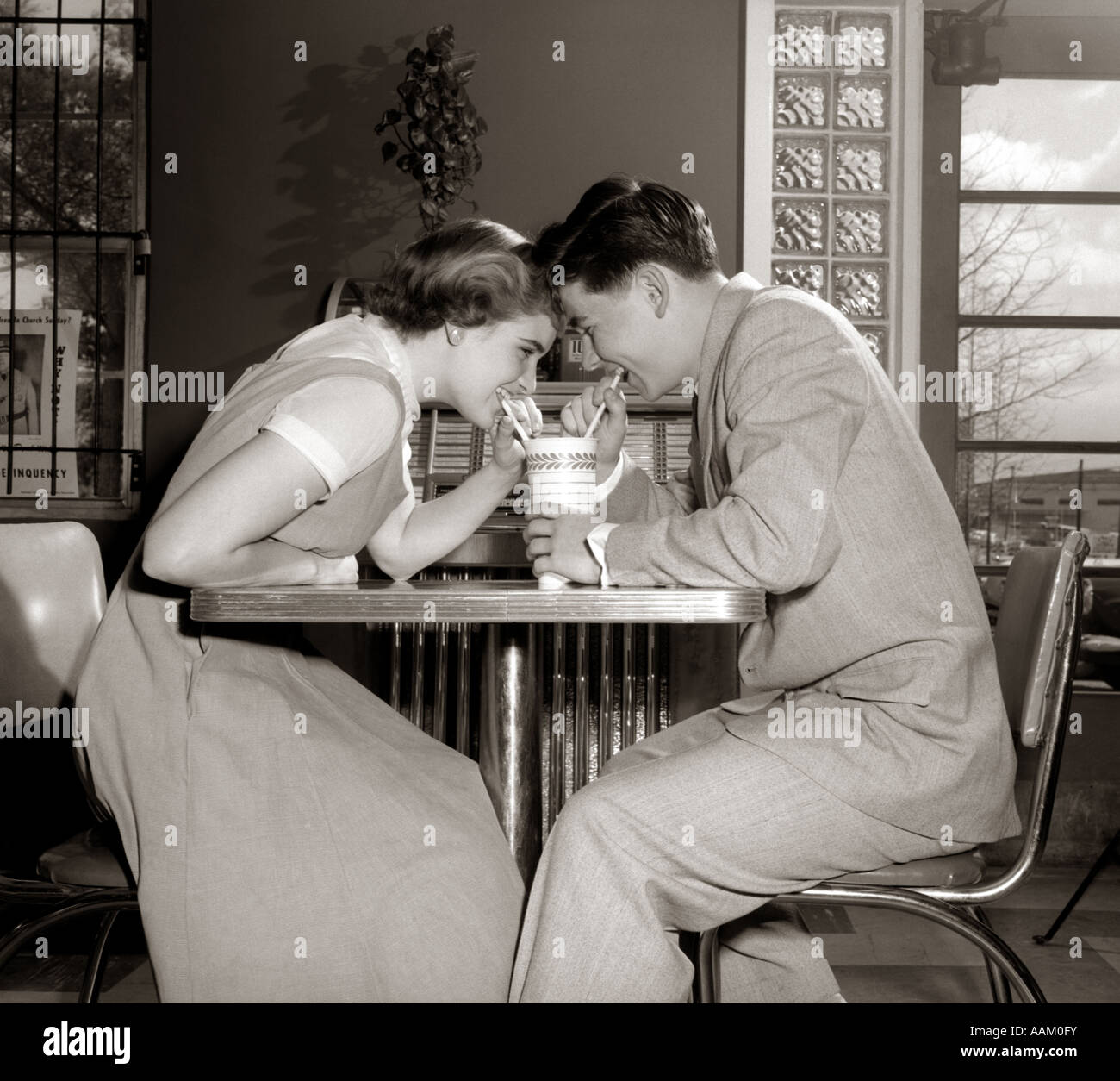 1950s 1960s LAUGHING TEENAGE COUPLE BOY AND GIRL SHARING DRINK TOGETHER WITH TWO STRAWS IN SODA SHOP