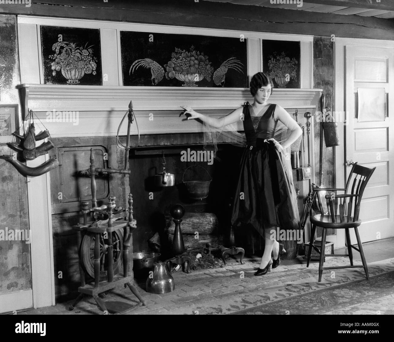 1920s WOMAN IN COCKTAIL DRESS STANDING IN FRONT OF LARGE FIREPLACE - Stock Image