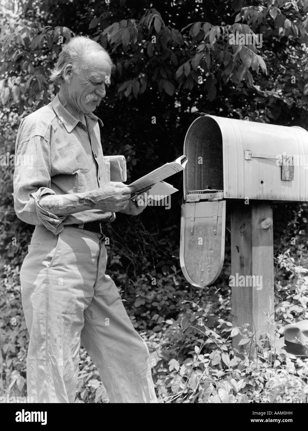 1940s SENIOR FARMER READING MAIL AT RURAL FREE DELIVERY MAIL BOX Stock Photo