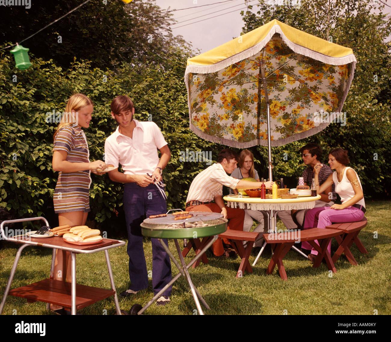 1970s GROUP TEENAGERS BOYS GIRLS BACKYARD GRILLING TABLE UMBRELLA - Stock Image