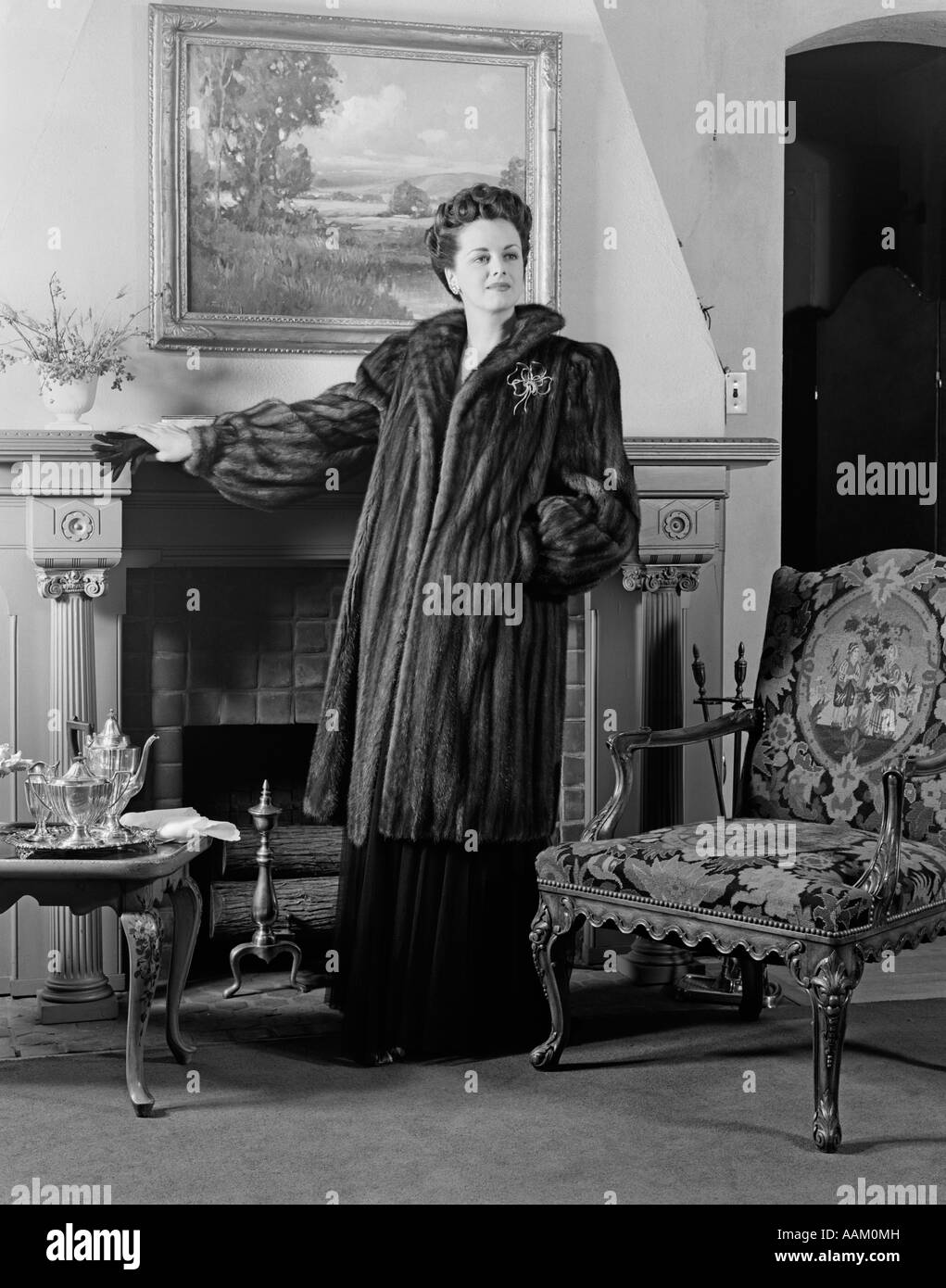 1940s WOMAN IN FORMAL LIVING ROOM STANDING IN FRONT OF FIREPLACE WEARING FULL-LENGTH FUR LOOKING AT CAMERA - Stock Image