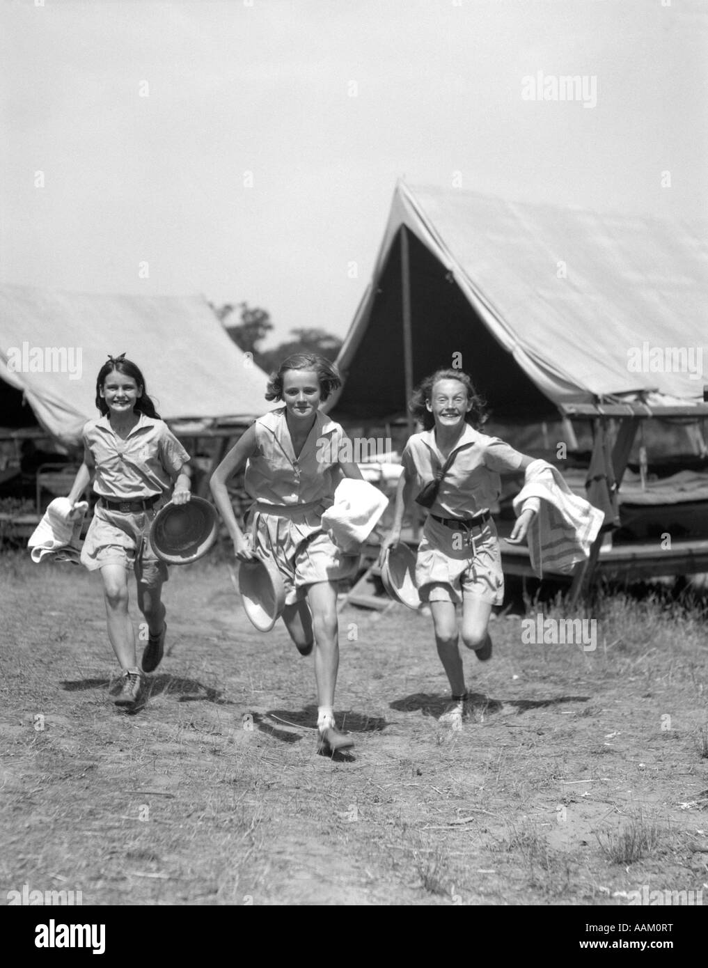 1930s THREE TEEN GIRLS WEARING CAMP SHORTS & SHIRTS RUNNING FROM TENTS WHILE HOLDING TOWELS & WASH BASINS - Stock Image