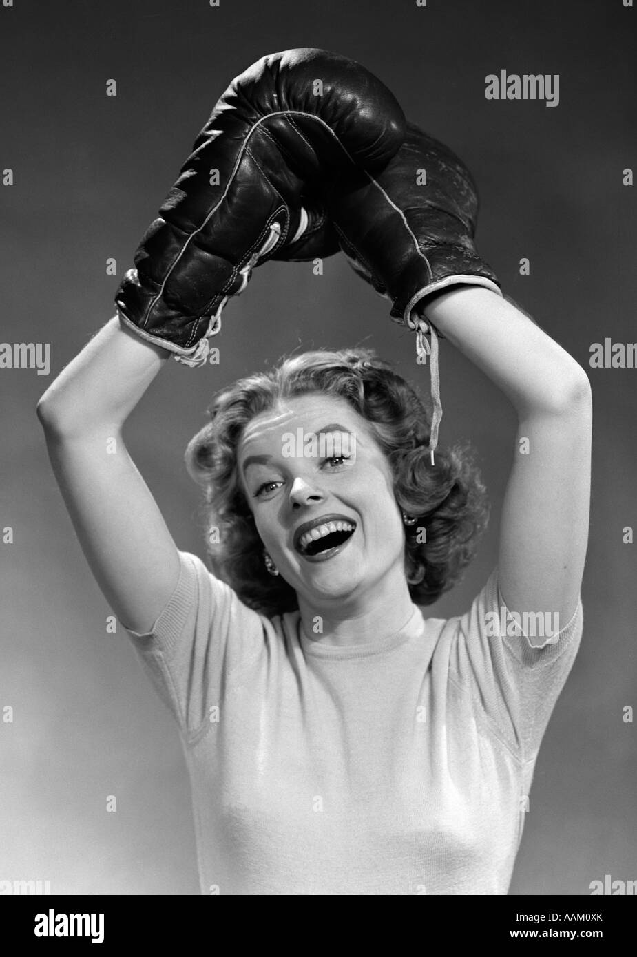 1950s PORTRAIT OF WOMAN WEARING BOXING GLOVES IN WINNING POSE ARMS RAISED OVERHEAD LOOKING AT CAMERA - Stock Image