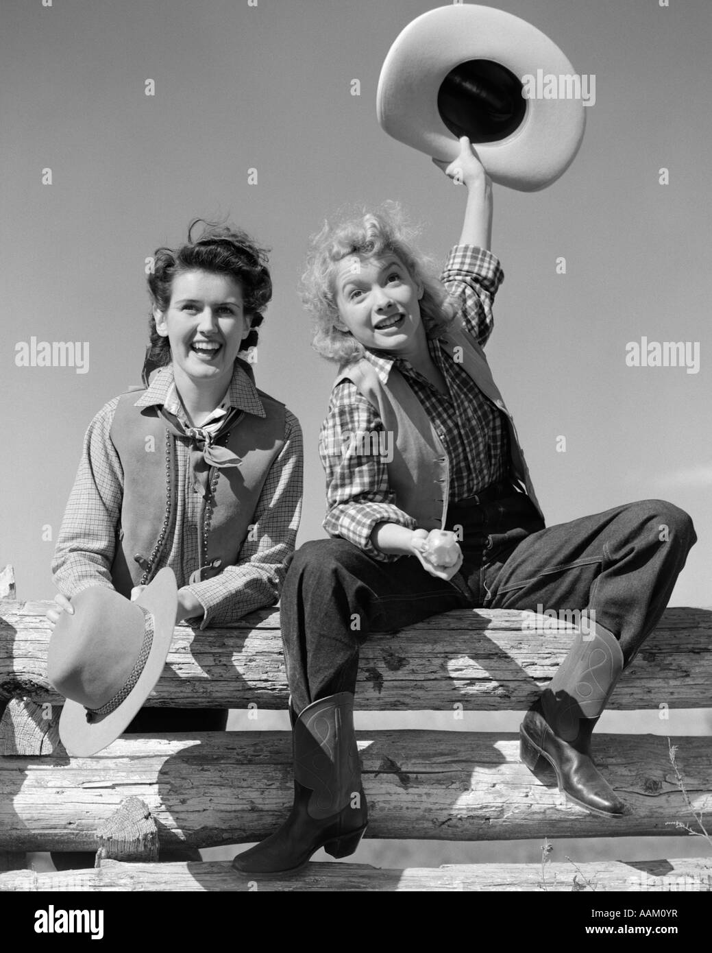 1940s TWO SMILING WOMEN IN COWBOY OUTFITS SITTING ON FENCE ONE RAISING HAT IN AIR OTHER STANDING BESIDE HER BOTH - Stock Image