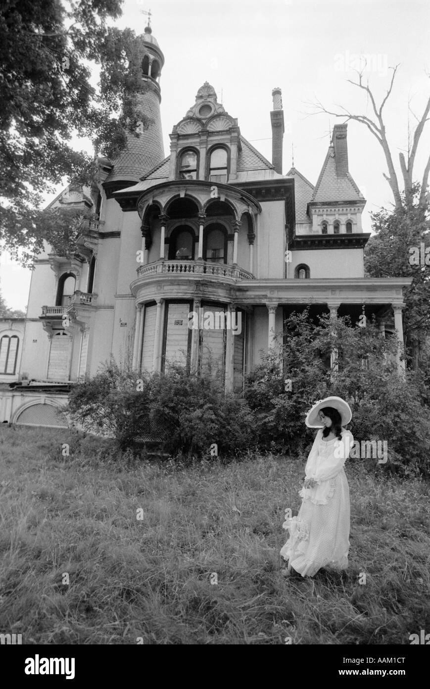 WOMAN IN VICTORIAN COSTUME STANDING ON FRONT LAWN OF LARGE VICTORIAN HOME - Stock Image