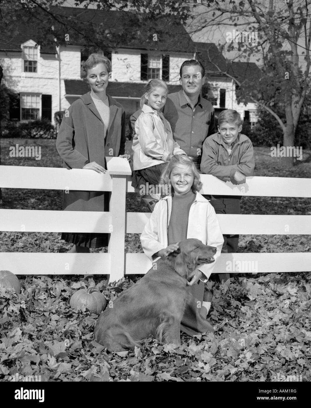 1960s FAMILY PORTRAIT FATHER MOTHER TWO DAUGHTERS SON AND DOG GATHERED AROUND WHITE FRONT YARD FENCE LOOKING AT - Stock Image