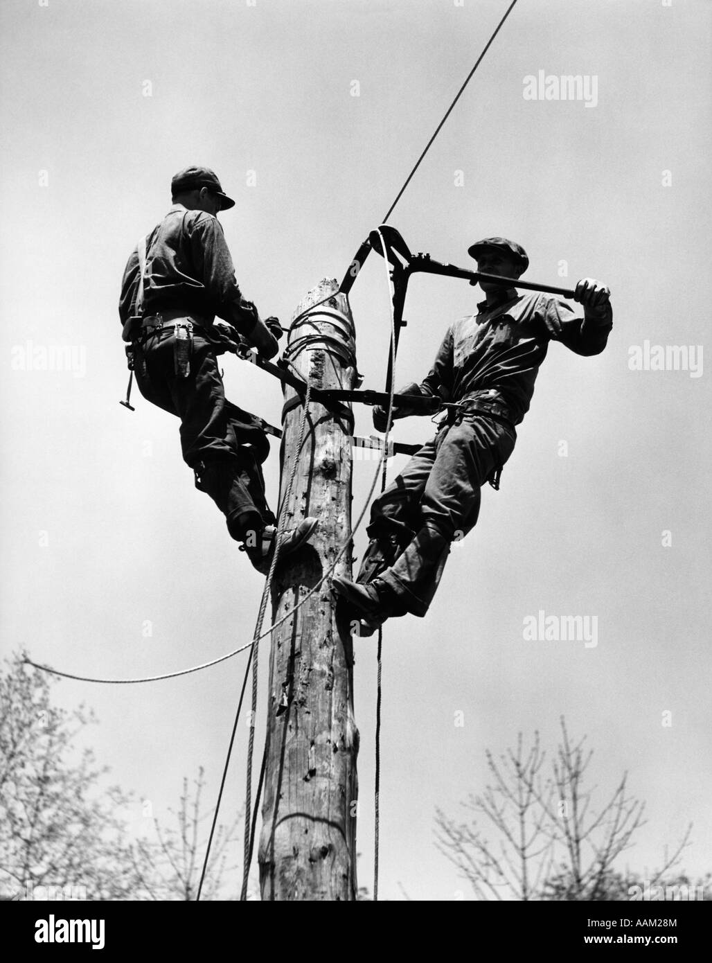 1930s 1940s Two Men Working On Electrical Power Pole Cutting Wire View