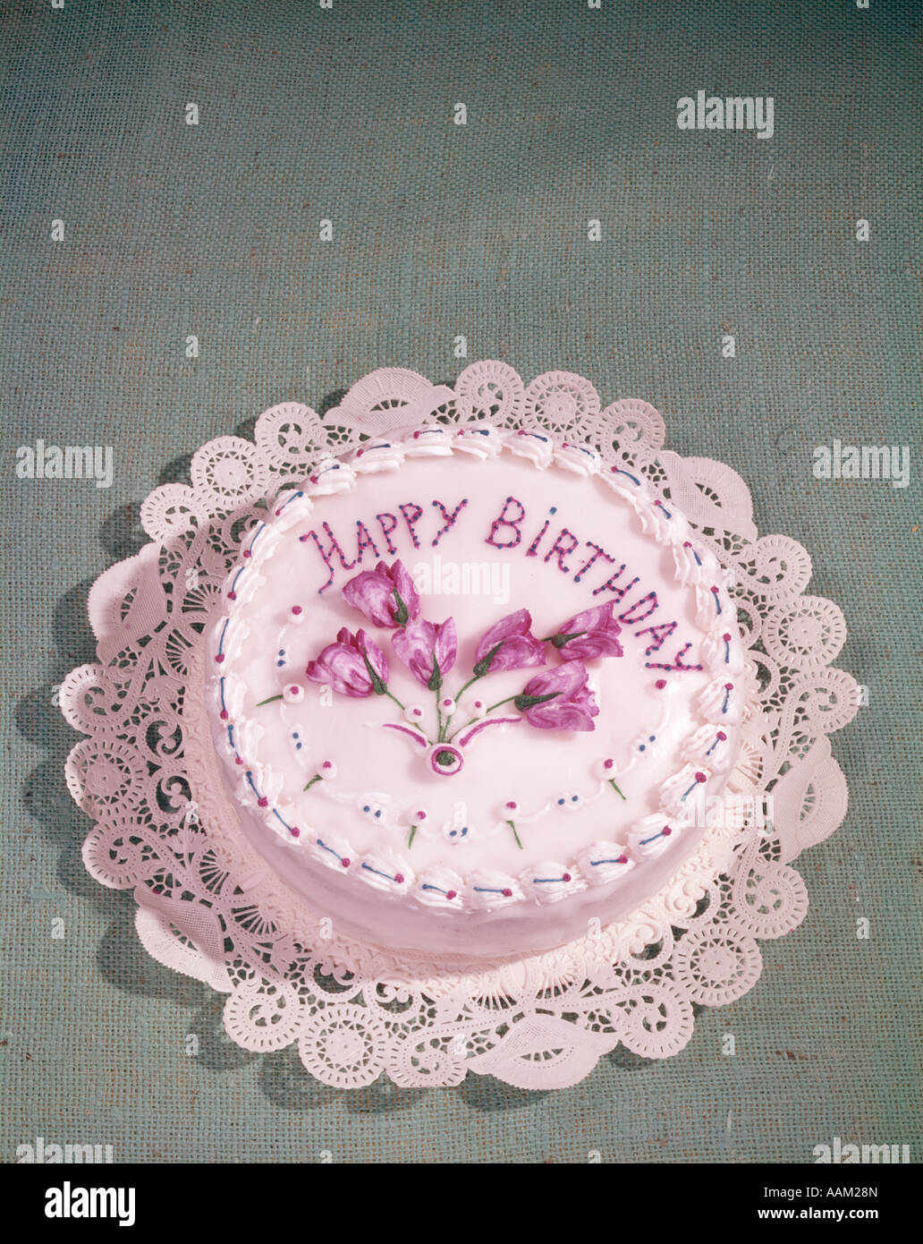 HAPPY BIRTHDAY CAKE WITH WHITE FROSTING AND PINK LETTERS AND FLOWERS - Stock Image