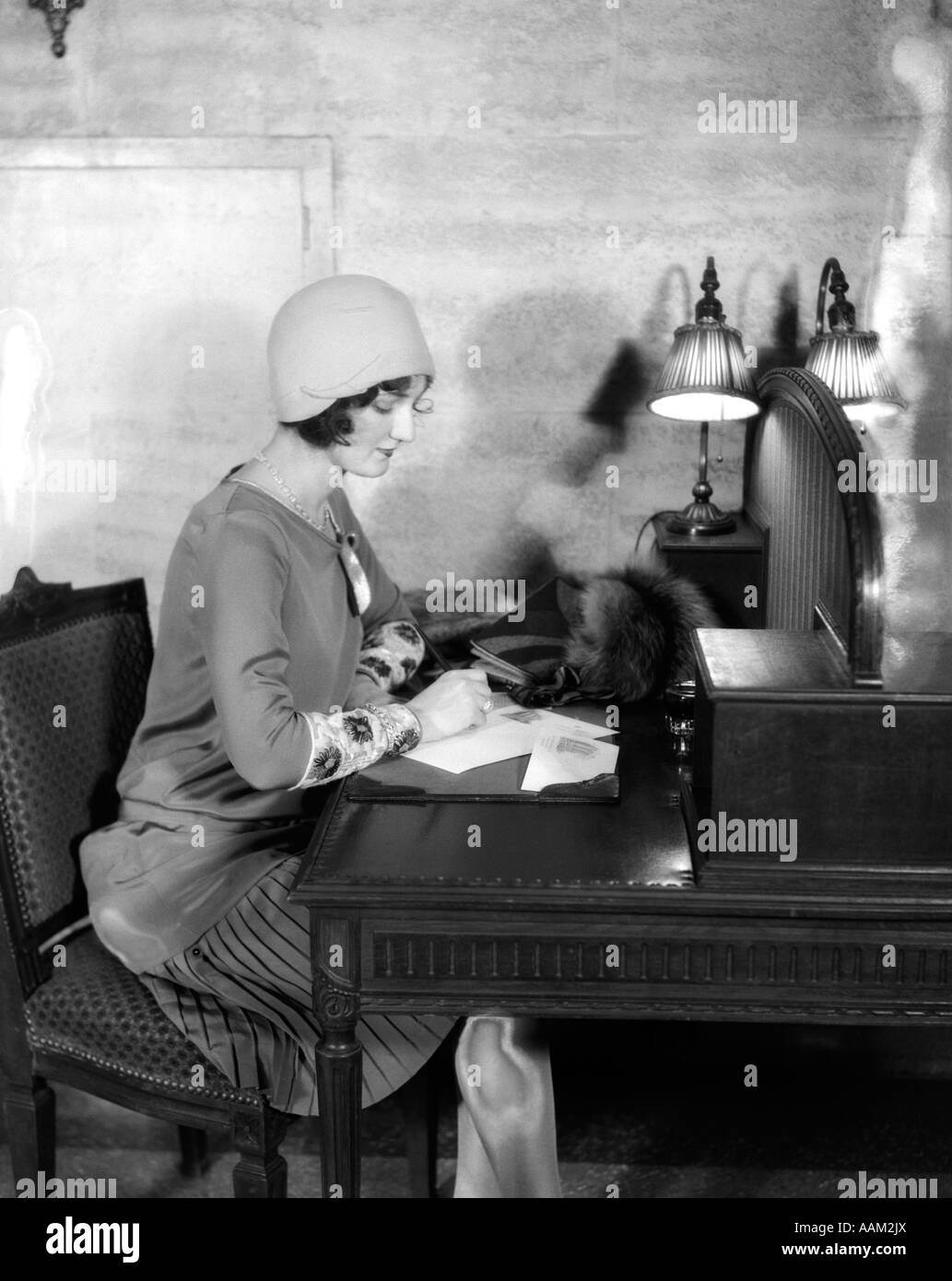 1920s WOMAN SITTING AT DESK WRITING LETTER BY LAMP FASHION CLOCHE HAT HOTEL LOBBY Stock Photo