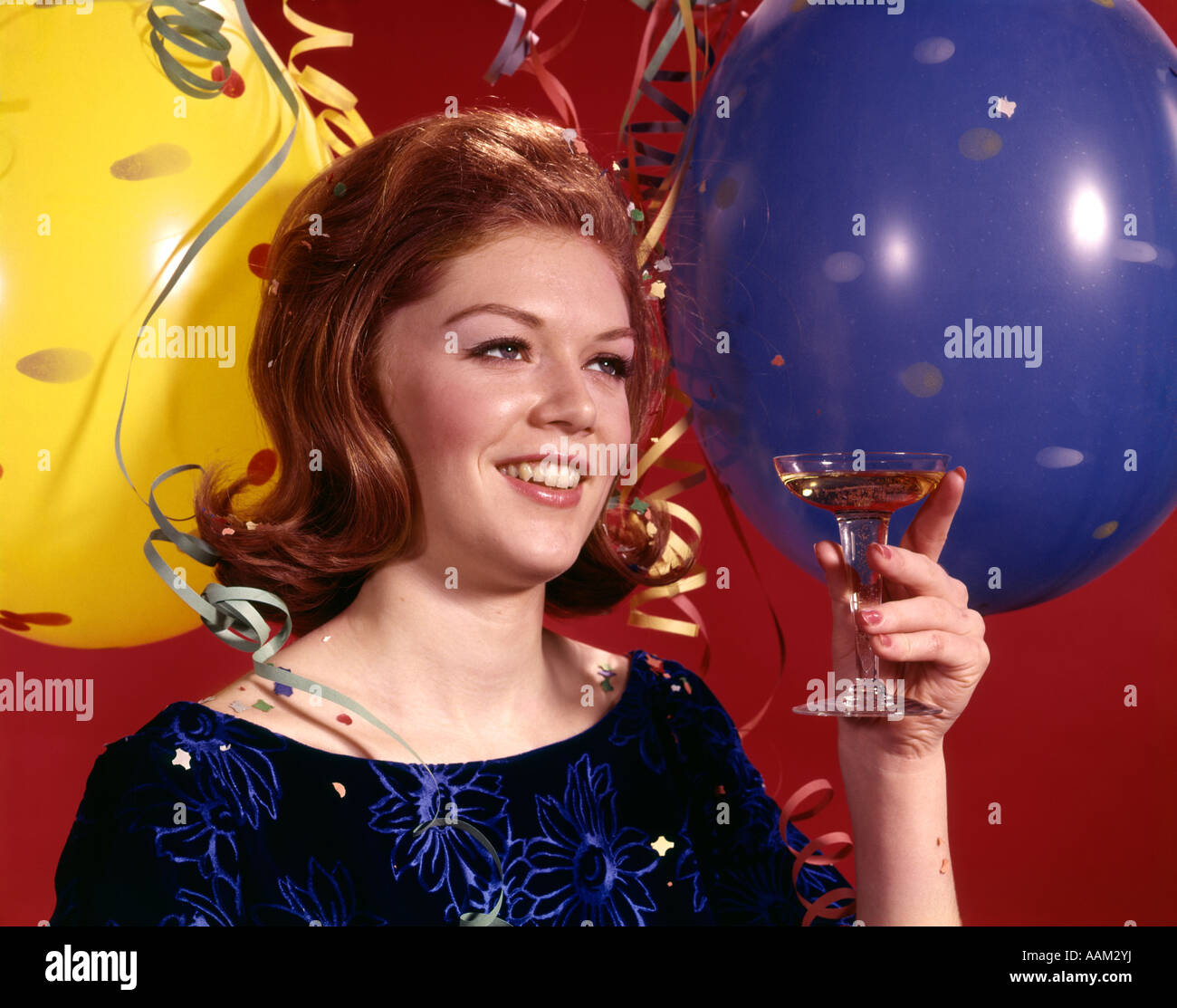 1960s YOUNG WOMAN SMILING TOASTING TOAST GLASS CHAMPAGNE BALLOONS STREAMERS BACKGROUND PARTY NEW YEARS - Stock Image